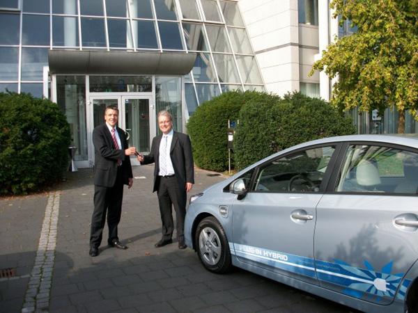 Sascha van Gool, Key Account Manager, Toyota Geschäftskunden Services, übergibt die Autoschlüssel für den Prius Plug-In Hybrid an Reinhard Hüning,Business Development Manager Public Sector, LeasePlan