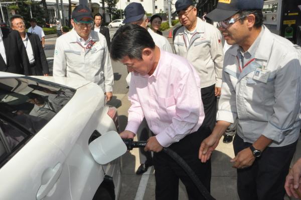 Japanischer Wirtschaftsminister beim Wasserstoff tanken